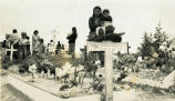 Families in cemetery with decorated graves, n.d.
