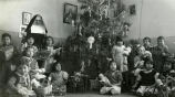 Children with gifts at Christmas tree, n.d.