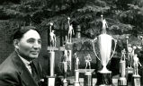 Coach Clifford with athletic trophies, n.d.