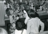 Sister Eileen Gran, O.S.F., distributing Christmas presents, 2 of 2, n.d.