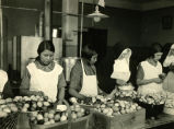 Students and religious sister handling eggs in kitchen, n.d.