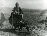 Older woman with dog pulling a travois, 1920