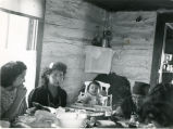 Family dining in log cabin home, n.d.