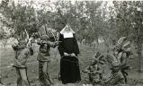 Boys portraying stereotypical Indians and Franciscan sister, n.d.