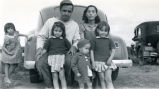 Parents with four chldren by their car, n.d.