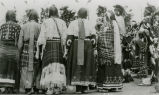 Women in regalia behind men dancers, n.d.