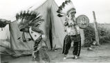 Two boys in chiefs' costumes singing and dancing, 1944