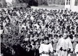 Children praying the rosary with Father Piefer, S.J., 1952