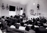 Children and teacher listening to homily at mass, n.d.