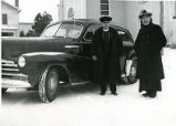 Father Harold Gibbons, S.J., and Father Eugene Buechel, S.J., by car, n.d.