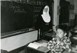 Elementary classroom with religious sister and boy, n.d.