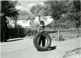 Boy playing with tire, n.d.