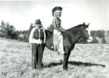 Mounted youth in regalia with man, n.d.