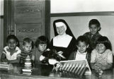 Kindergarten students with toys and Franciscan sister, n.d.