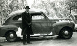 "Father """"Mac"""" McNamara, S.J., by automobile in snow, 1951"