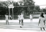 Girls playing volleyball outdoors, n.d.