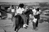 Father Sheehan, S.J., and children on horseback, 1985