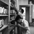 Boys by library books stacks, 1972
