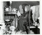 Mrs. Black Buffalo seated in a tent with dog, 1955