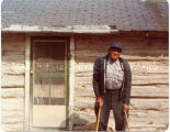 Andrew Left Hand standing with two canes  in front of log cabin home, n.d.