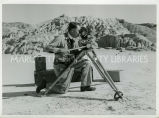 Father Scott, S.J., shooting film in badlands, n.d.