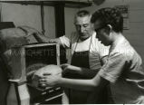 Brother Bill Siehr supervising boy slicing bread with a machine, S.J., n.d.