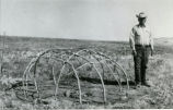 Jesse Steed at sweat lodge frame with rocks and fire pit, 1956