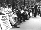 Dorothy Day and others seated in protest of civil defense drill, 1956