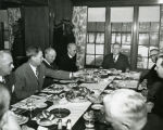 A group of men gather around the table for a meal