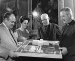Donors and university officials examine a model of the Saint Joan of Arc Chapel site