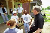 Robert A. Wild, S.J., visits a Habitat for Humanity site and converses with the volunteers, 1999