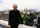 John P. Raynor, S.J., stands on top of the Schroeder Complex, with the Marquette campus behind...