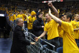 Robert A. Wild, S.J., greets students at a men's basketball game, 2003