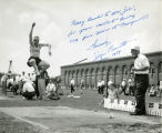 John Bennett competes in long jump at outdoor meet, 1954