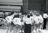 "Catherine ""Tat"" Shiely in volleyball team huddle, 1983"