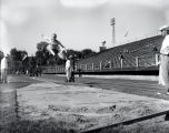 John Bennett in midst of long jump, 1951-1952