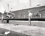 John Bennett practicing broad jump at Marquette Stadium, 1951-1952