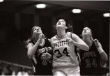 Abbie Willenborg and two opponents watch the basketball, 1998