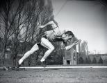 Side view of John Bennett practicing start of sprint, 1951-1952