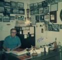 Coach Shimek sitting behind his desk, 1976