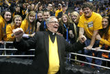 President Robert A. Wild, S.J., cheers with students at men's basketball game, 3 of 4, 2011