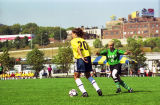Rhegan Hyypio looks to kick the soccer ball as an opponent closes in, 1999