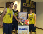 Basketball players Scott Merritt, Steve Novak and Travis Diener pose for a food drive event, 2003