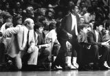 Lloyd Walton watches the basketball team from the sidelines and provides coaching instruction, 1984