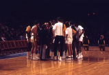 Al McGuire instructs basketball team in huddle, 1971