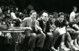 Hank Raymonds, Rick Majerus, and other team members watch a game from the sidelines, 1983