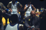 Hank Raymonds and Rick Majerus coach team in a huddle, 1977-1978