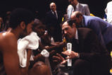 Hank Raymonds and Rick Majerus coach players in a huddle, 1978-1979