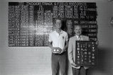 Keith Hanson and John Bennett pose in front of track and field record board, 1986
