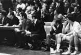 Al McGuire and Hank Raymonds watch game from sidelines, 1972